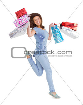 Smiling brunette jumping while holding shopping bags
