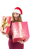 Surprised pretty brunette in santa hat opening gift