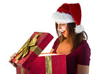 Pretty woman in santa hat opening a gift smiling at it