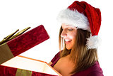 Pretty brunette in santa hat opening a gift