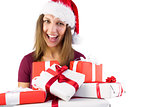 Smiling brunette in santa hat holding pile of gifts