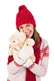 Cute brunette in warm clothing hugging teddy bear