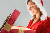 Pretty santa girl opening a gift