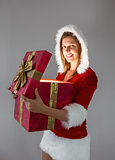 Smiling girl opening a gift and looking at the camera