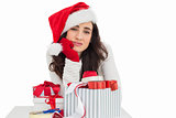 Unsure brunette in santa hat packing gifts