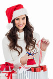 Smiling brunette in santa hat packing gifts