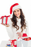 Cheerful brunette in santa hat holding gift