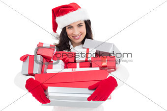 Smiling brunette in santa hat holding stack of presents