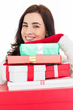 Portrait of a smiling brunette holding pile of gifts