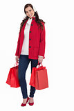 Happy brunette in winter clothes holding shopping bags