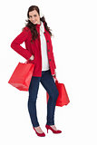 Cheerful brunette in winter clothes posing and holding shopping bags