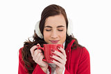 Woman in winter clothes enjoying a hot drink eyes closed