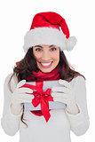Festive brunette in santa hat holding gift