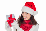 Excited brunette in santa hat showing gift