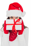 Brunette in red gloves and santa hat showing gift