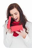 Surprised brunette opening christmas gift