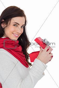 Smiling brunette opening christmas present