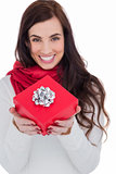 Happy brunette holding red gift with a bow