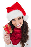 Happy brunette holding christmas gift