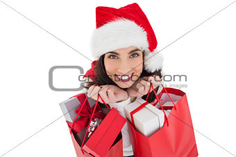 Smiling brunette holding shopping bags full of gifts
