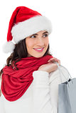 Smiling brunette in santa hat holding shopping bag