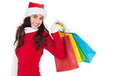 Festive brunette in winter wear holding shopping bags