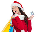 Festive brunette holding shopping bags and credit card