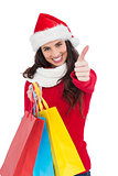 Festive brunette holding gifts and thumb up