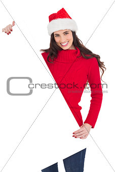 Smiling brunette in santa hat showing white poster