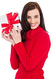 Smiling brunette in red jumper hat showing a gift