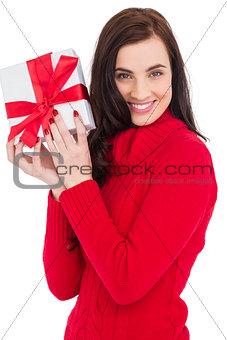 Smiling brunette in red jumper hat showing a gift