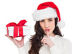 Festive brunette holding gift and keeping a secret