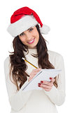 Smiling brunette writing her christmas list