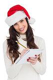 Smiling brunette writing her christmas list