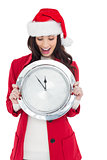 Excited brunette holding a clock