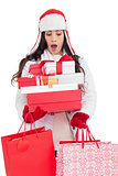 Surprised brunette in winter clothes holding many gifts and shopping bags