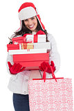 Brunette in winter clothes holding many gifts and shopping bags