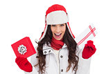Excited brunette in winter clothes holding gifts