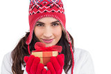 Smiling brunette in winter clothes holding gift