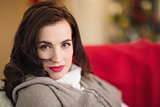 Serious brunette relaxing on the couch at christmas