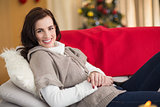 Happy brunette relaxing on the couch at christmas