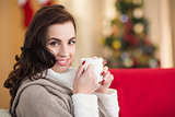 Smiling brunette holding a mug of hot chocolate at christmas