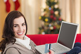 Brunette shopping online with laptop at christmas