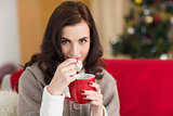 Brunette holding mug and eating marshmallow at christmas