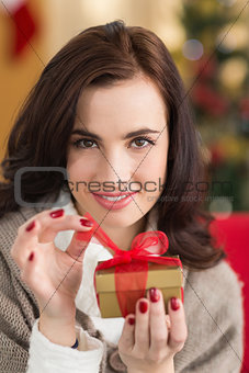 Smiling brunette opening a gift on christmas day