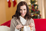 Brunette opening a gift on the couch at christmas