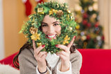 Brunette on the couch showing wreath at christmas