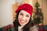 Portrait of a smiling brunette in hat at christmas