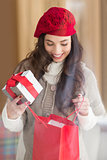 Happy brunette holding gift and looking in gift bag