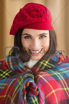 Smiling brunette with cover and red hat
